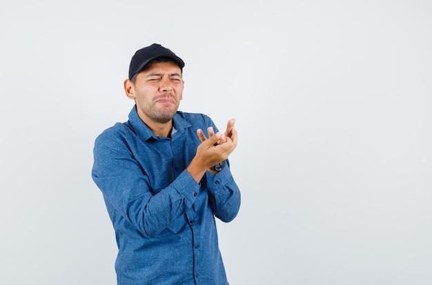 Junger mann leidet unter schmerzhafter hand im blauen hemd, mütze, vorderansicht.