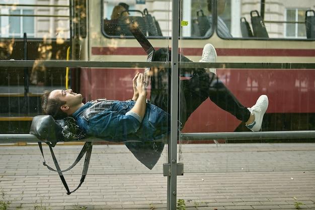 Junger mann liegt auf der straßenbahnhaltestelle mit notizbuch auf den knien.