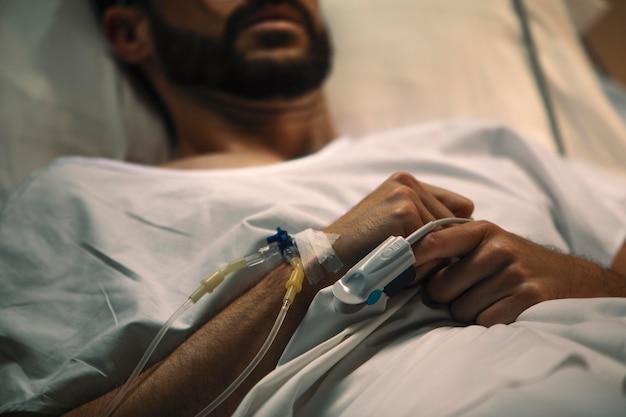 Junger mann liegt krank in einem krankenhausbett