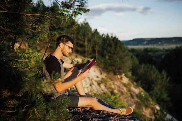 Junger mann liest buch, während er gegen schöne naturlandschaft sitzt.