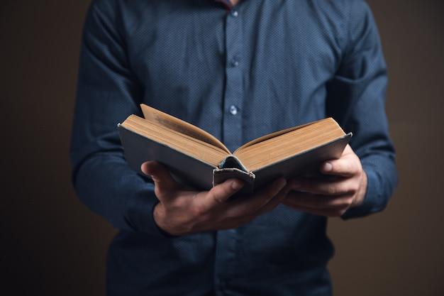 Junger mann liest ein buch auf brauner oberfläche