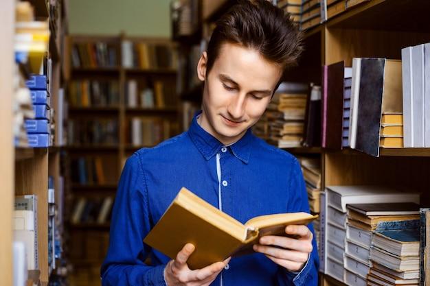 Junger mann liest ein buch in der bibliothek
