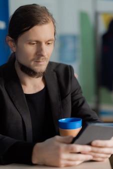 Junger mann liest ein neues buch auf seinem tablett mit einem kaffee