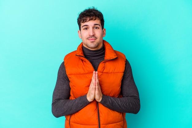 Junger mann lokalisiert auf blauer wand betend, zeigt hingabe, religiöse person, die nach göttlicher inspiration sucht