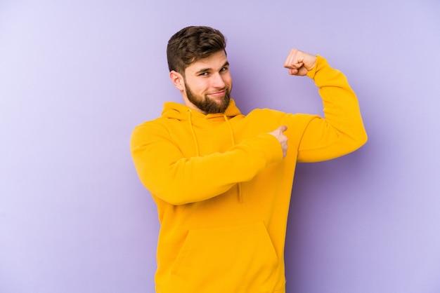 Junger mann lokalisiert auf lila hintergrund, der kraftgeste mit armen zeigt, symbol der weiblichen macht