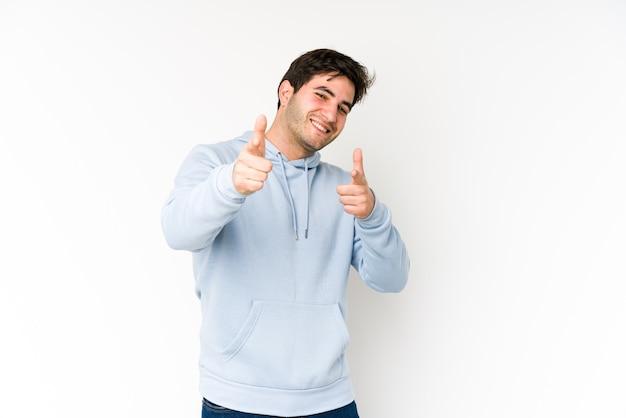 Junger mann lokalisiert auf weißem hintergrund, der mit den fingern nach vorne zeigt.