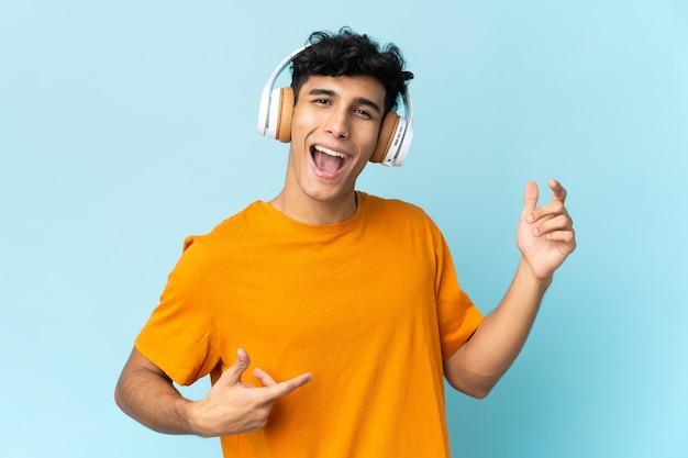 Junger mann lokalisiert auf weißem hintergrund, der musik hört
