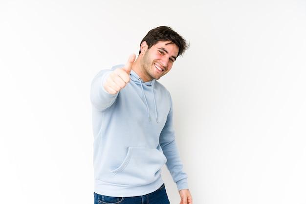 Junger mann lokalisiert auf weißem hintergrund lächelnd und daumen hoch