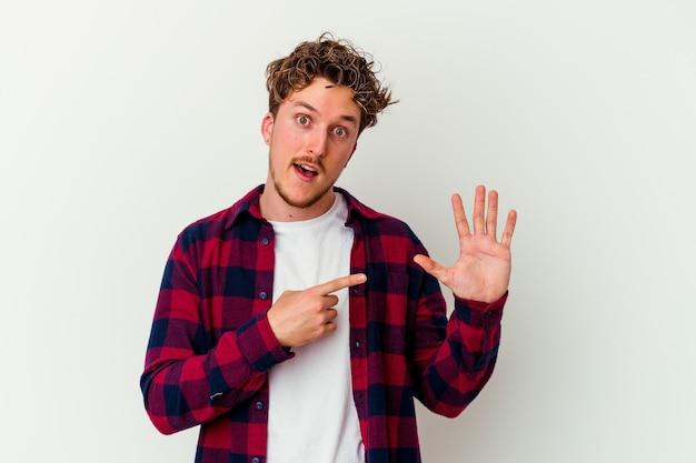 Junger mann lokalisiert auf weißer wand, die fröhlich lächelnd zeigt nummer fünf mit den fingern
