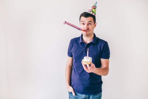 Junger mann lokalisiert über weißem hintergrund. kerl halten kleinen kuchen mit kerze auf ihm, der geburtstag feiert. einsam auf party. allein feiern.