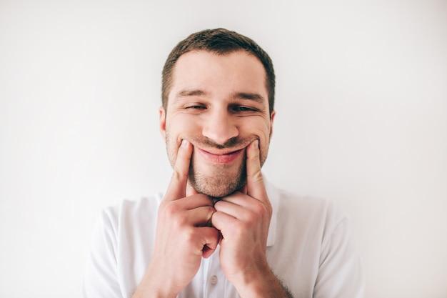 Junger mann lokalisiert über weißer wand. gesichtsporträt des kerls, der mit kraft lächelt. finger an den lippenrändern halten.