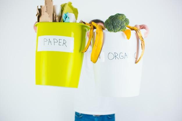 Junger mann lokalisiert über weißer wand. guy versteckt sich hinter zwei eimern mit getrenntem papier und organischem abfall. sortierte materialien für den recyclingprozess.