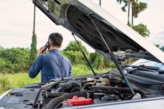 Junger mann machen einen anruf während des defekten autos. der mensch braucht hilfe.