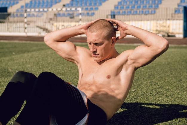 Junger mann macht crunches beim training der bauch- und brustmuskulatur im stadion
