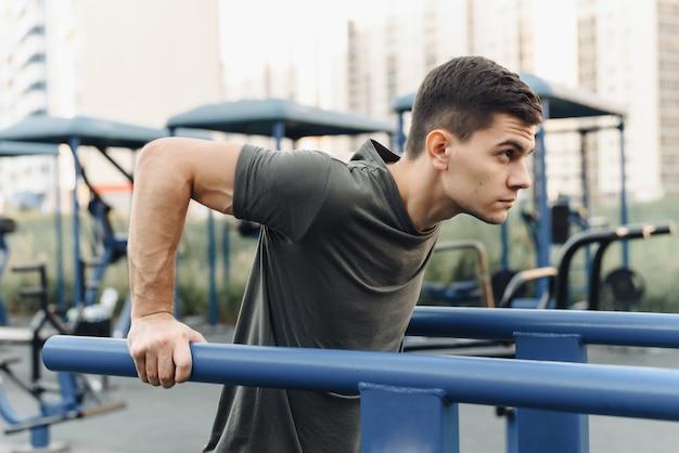 Junger mann macht dips auf den stufenbarren