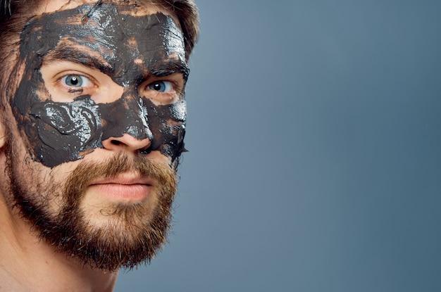 Junger mann macht eine gesichtsmaske, hautpflege für männer