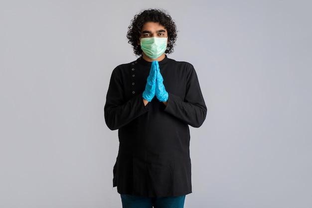 Junger mann macht namaste wegen ausbruch von covid-19. neue begrüßung, um die ausbreitung von coronavirus zu vermeiden, anstatt mit einer umarmung oder einem händedruck zu begrüßen. yoga-praxis für das geistige gleichgewicht.