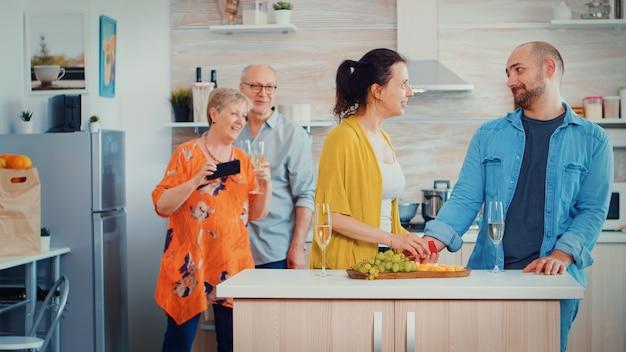 Junger mann macht seiner freundin vor den eltern einen vorschlag, während sie am familientag zu hause in der küche sprechen. sie steckt sich den ring an den finger, küsst und umarmt ihn, mutter macht fotos