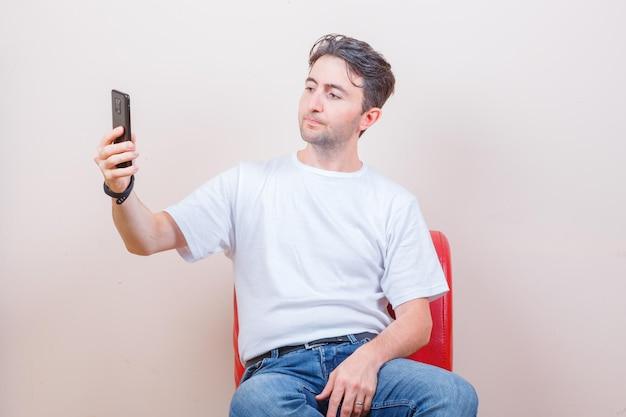 Junger mann macht selfie auf dem handy, während er auf einem stuhl in t-shirt, jeans sitzt