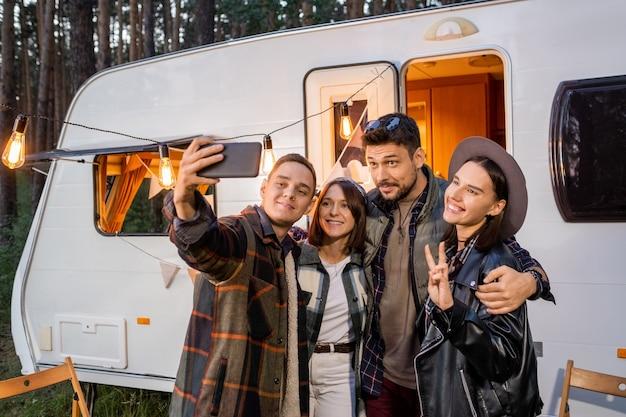 Junger mann macht selfie mit freunden mit dem wohnmobil