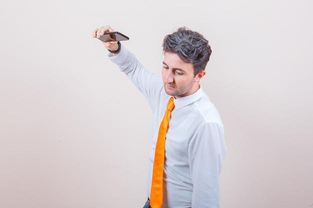 Junger mann macht sich bereit, handy im hemd wegzuwerfen
