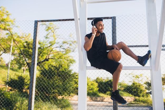 Junger mann macht sport, hat spaß und hört musik über kopfhörer