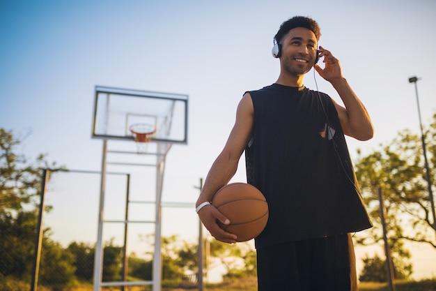 Junger mann macht sport, spielt basketball bei sonnenaufgang, hört musik über kopfhörer