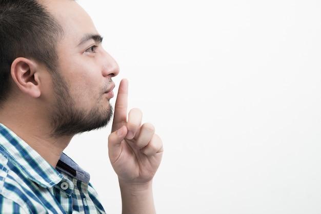 Junger mann macht stille geste isoliert auf weißem hintergrund.