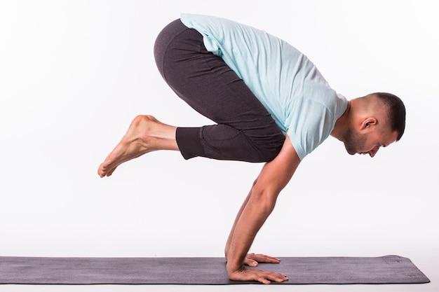 Junger mann macht yoga lokalisiert über weißem hintergrund