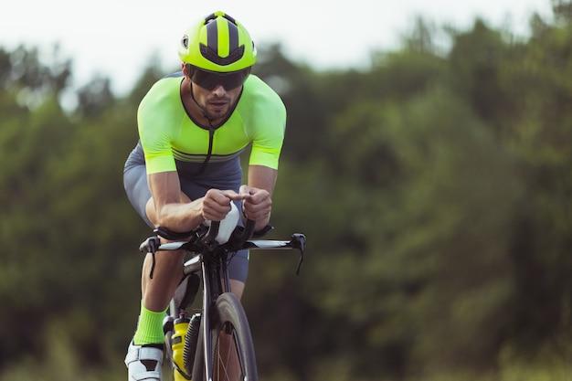 Junger mann, männlicher triathlon-athlet, der an sportwettbewerben im freien teilnimmt