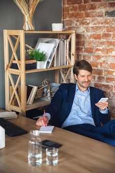 Junger mann, manager, team führte nach der quarantäne die rückkehr zur arbeit in sein büro, fühlt sich glücklich und inspiriert