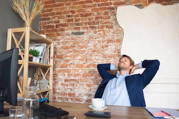Junger mann, manager, teamgeführter rückkehr zur arbeit in seinem büro nach quarantäne, fühlt sich glücklich