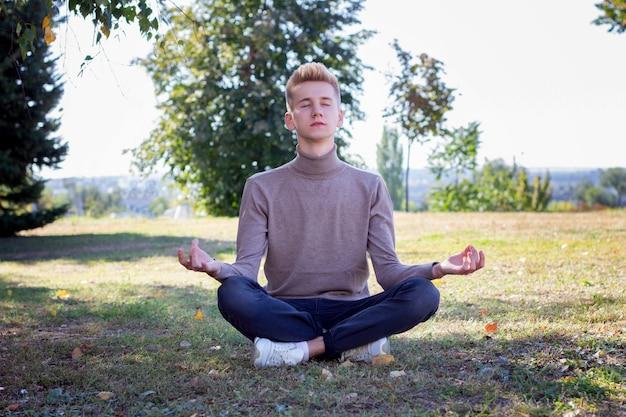 Junger mann meditiert im park. unter die inschrift setzen.