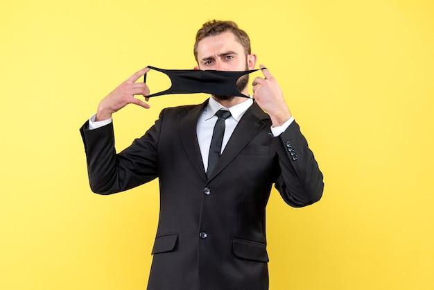 Junger mann mit anzug und krawatte, der seine maske trägt, um eine infektion durch koronavirus auf gelb zu verhindern
