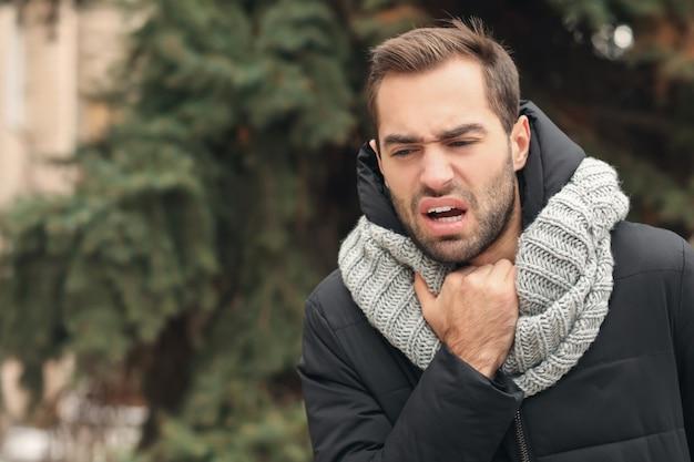 Junger mann mit asthmaanfall im freien