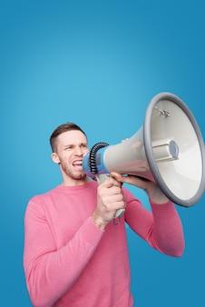 Junger mann mit ausdrucksstarkem gesicht, das ansage ins megaphon spricht