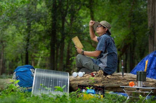 Junger mann mit ausrüstung für das kampieren und solarenergiekasten