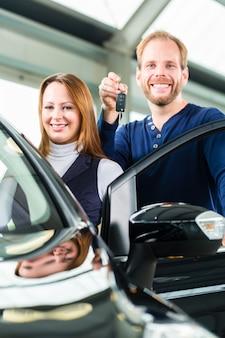 Junger mann mit auto im autohaus
