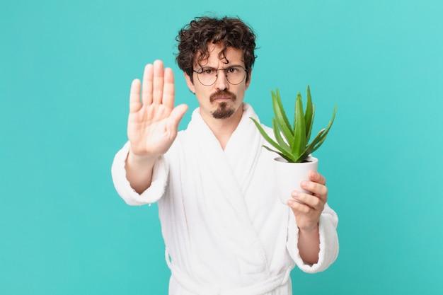 Junger mann mit bademantel, der ernst aussieht und offene handfläche zeigt, die stopp-geste macht