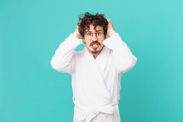 Junger mann mit bademantel, der sich gestresst, ängstlich oder ängstlich fühlt, mit den händen auf dem kopf
