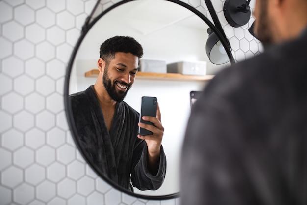 Junger mann mit bademantel drinnen im badezimmer zu hause unter selfie