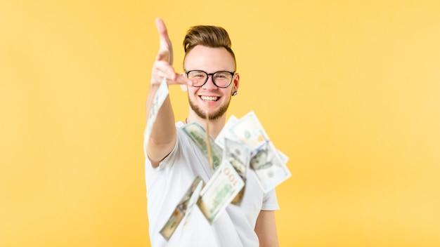 Junger mann mit bärtigem hipster-zahnlächeln, der dollar auf sie wirft banknoten in der luft. banking marketing commerce cashback