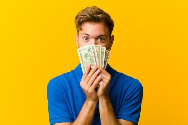 Junger mann mit banknoten gegen orange