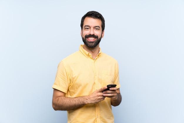 Junger mann mit bart auf dem blau, das eine mitteilung mit dem mobile sendet