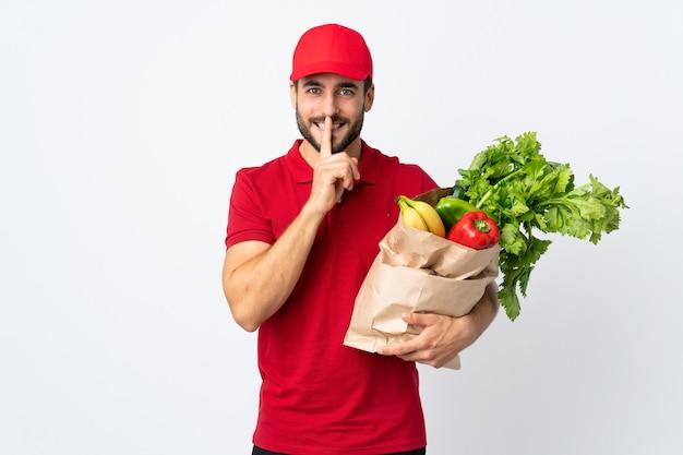 Junger mann mit bart, der eine tüte voll gemüse lokalisiert auf weißem hintergrund hält, der schweigegeste tut
