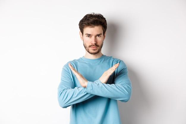 Junger mann mit bart, der ernst aussieht, kreuzgeste macht, um etwas zu stoppen, handlung zu verbieten, gegen weißen hintergrund stehend