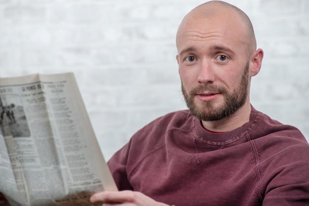 Junger mann mit bart die zeitung lesend