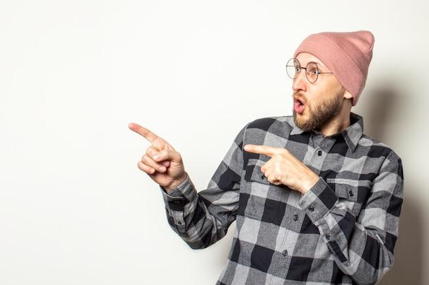 Junger mann mit bart im hut, kariertem hemd und brille zeigt mit den fingern zur seite mit einem überraschten gesicht auf einem isolierten weiß. geste schau es dir an