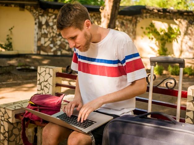 Junger mann mit bart in der zufälligen kleidung des sommers, die an laptop mit gepäck der großen taschen in der stadt arbeitet