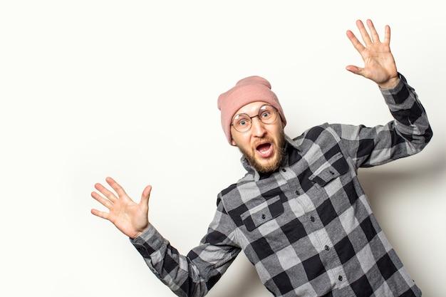 Junger mann mit bart in hut, kariertem hemd und brille schaut von der seite mit einem überraschten gesicht auf einem isolierten weiß. gestenüberraschungsschock